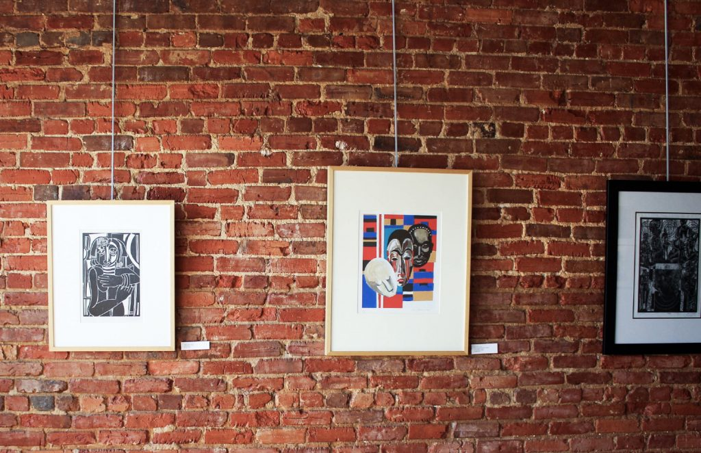 three paintings hanging on a brick wall